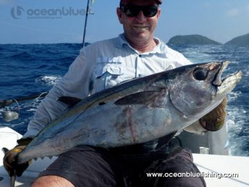 a very happy angler holding a dogtooth tuna
